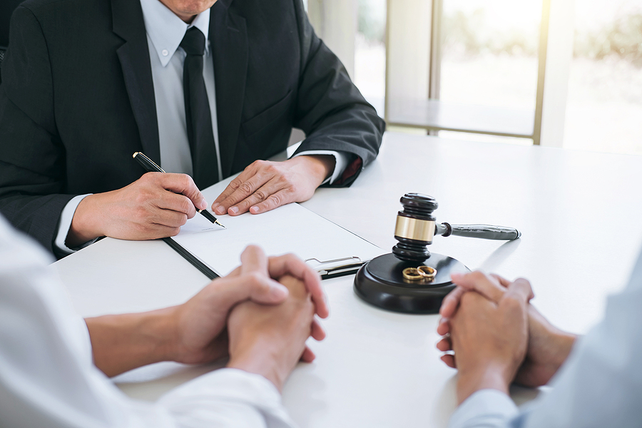 Lawyer assisting a couple in signing a prenup